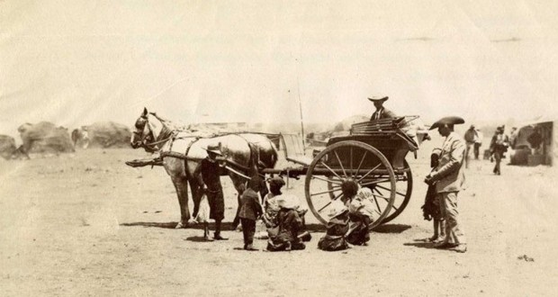 Pictured is an African family in and around a Cape cart in Kimberley